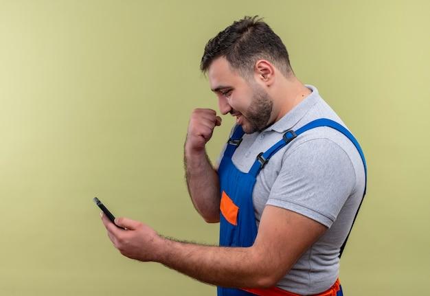 Uomo giovane costruttore in costruzione uniforme tenendo lo smartphone guardando lo schermo stringendo il pugno felice ed uscito