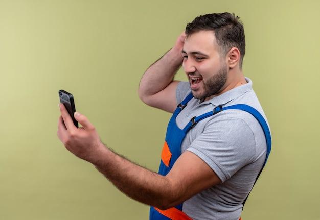 Uomo giovane costruttore in uniforme da costruzione tenendo lo smartphone guardando lo schermo di collegamento con qualcuno