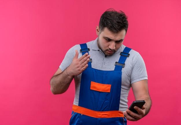 Uomo giovane costruttore in uniforme da costruzione tenendo lo smartphone guardando lo schermo scontento e confuso