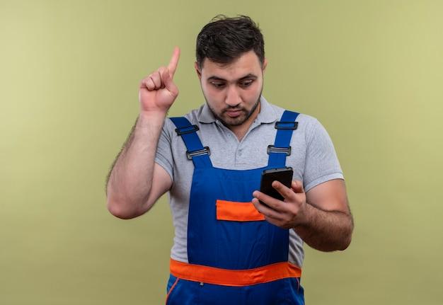 Uomo giovane costruttore in uniforme da costruzione tenendo lo smartphone guardando lo schermo puntare il dito verso l'alto ricordando a se stesso