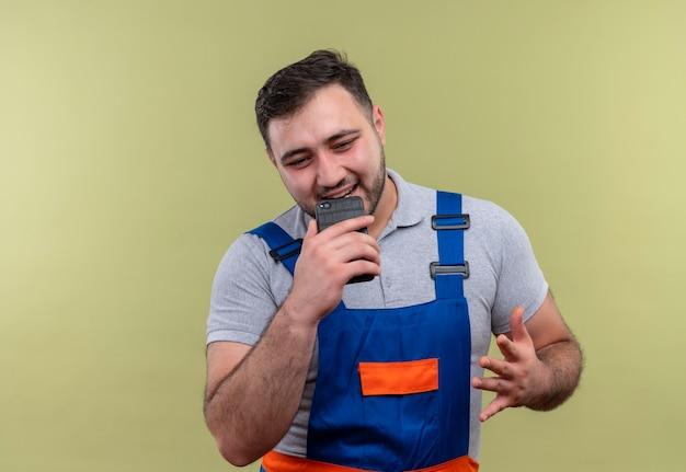 Uomo giovane costruttore in uniforme da costruzione tenendo lo smartphone inviando un messaggio vocale a qualcuno