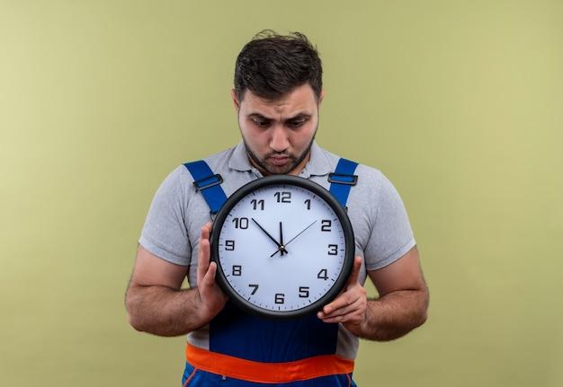 Uomo giovane costruttore in uniforme di costruzione che tiene orologio da parete che sembra confuso e sorpreso