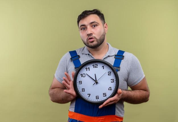 Uomo del giovane costruttore in orologio da parete della tenuta dell'uniforme della costruzione che sembra sorpreso