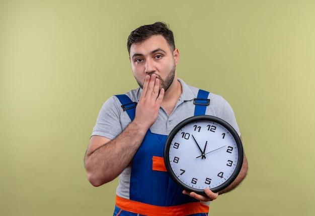 Giovane costruttore in uniforme di costruzione che tiene l'orologio da parete scioccato che copre la bocca con la mano