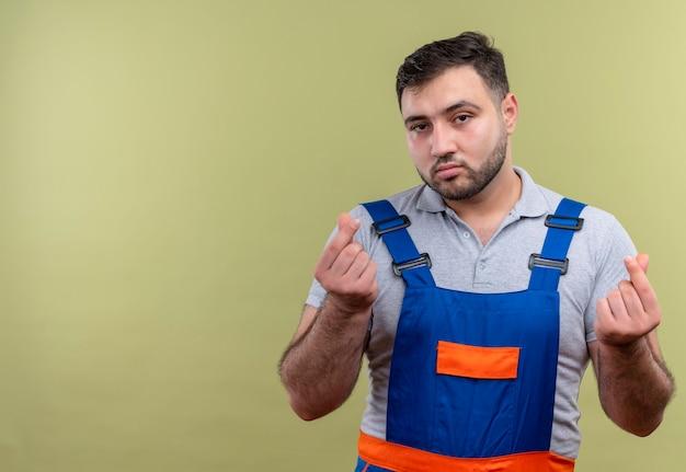 Uomo giovane costruttore in uniforme di costruzione che guarda l'obbiettivo con viso serio strofinando le dita chiedendo soldi