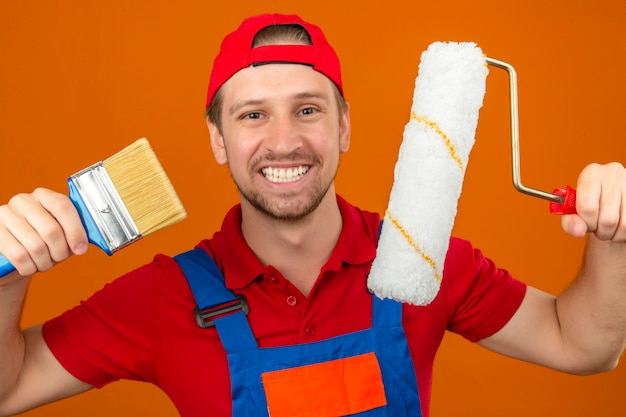 Young builder man in construction uniform and red cap holding paint roller and brush with big smile on face over isolated orange wall