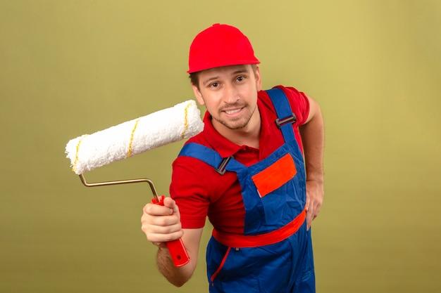 Giovane uomo del costruttore in uniforme della costruzione e rullo di pittura della tenuta dello spiritello malevolo con il grande sorriso sul fronte sopra la parete verde isolata