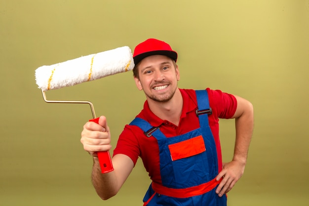 Young builder man in construction uniform and red cap holding paint roller with big smile on face over isolated green wall