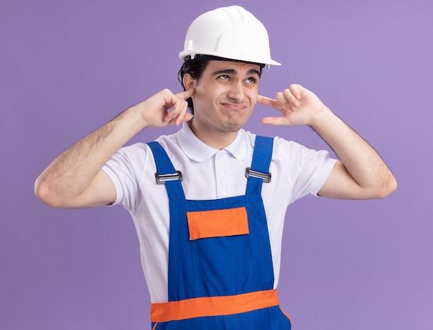 Uomo giovane costruttore in uniforme da costruzione e casco di sicurezza chiudendo le orecchie con le dita con espressione infastidita in piedi sopra la parete viola