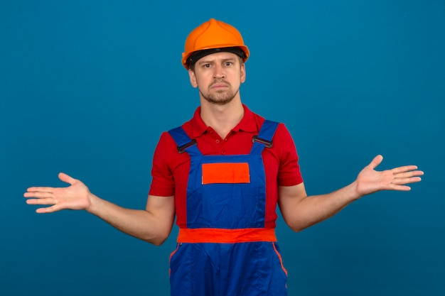 Young builder man in construction uniform and safety helmet clueless and confused expression with arms and hands raised doubt concept over isolated blue wall
