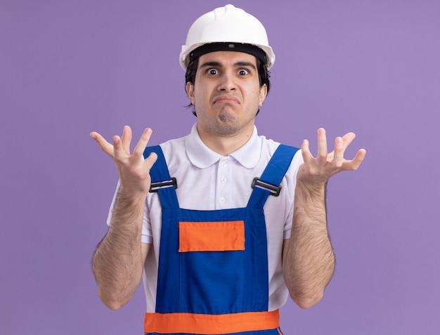 Giovane costruttore in uniforme da costruzione e casco di sicurezza confuso e sorpreso con le braccia alzate guardando davanti in piedi sopra il muro viola