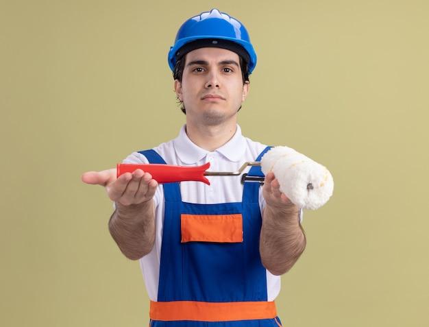 Giovane costruttore in uniforme da costruzione e casco di sicurezza che dimostra il rullo di vernice guardando la parte anteriore con la faccia seria in piedi sopra la parete verde