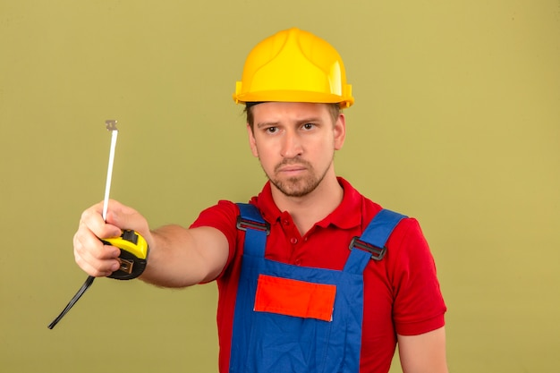 Young builder man in construction uniform and safety helmet giving to someone tape-line with serious face over isolated green wall