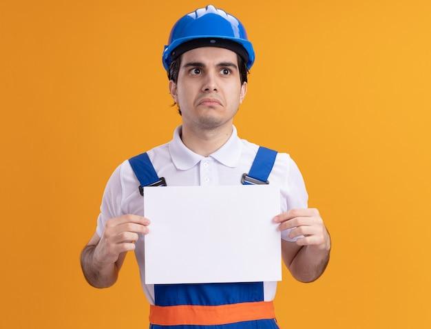 Uomo giovane costruttore in uniforme da costruzione e casco di sicurezza che tiene la pagina vuota che guarda da parte con l'espressione triste sul viso in piedi sopra la parete arancione
