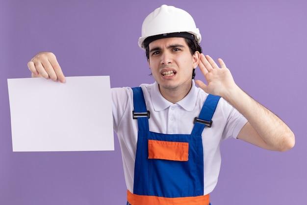 Uomo giovane costruttore in uniforme da costruzione e casco di sicurezza che tiene la pagina vuota guardando davanti con la mano sull'orecchio cercando di ascoltare i pettegolezzi in piedi sopra il muro viola