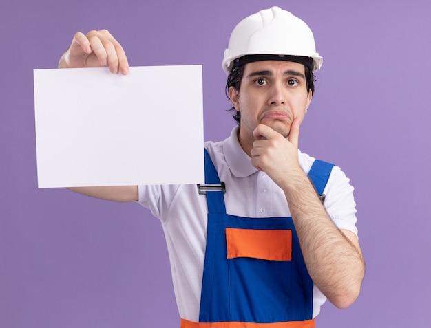 Uomo giovane costruttore in uniforme da costruzione e casco di sicurezza che tiene la pagina vuota guardando davanti con espressione triste che increspa le labbra in piedi sopra la parete viola