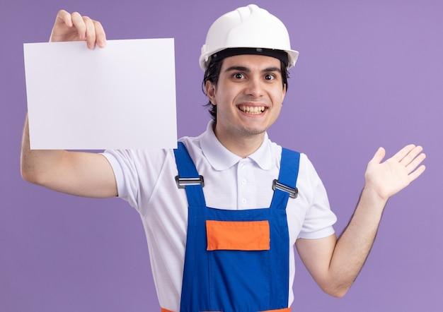 Uomo del giovane costruttore in uniforme da costruzione e casco di sicurezza che tiene la pagina vuota che guarda davanti con il sorriso sul viso in piedi sopra la parete viola