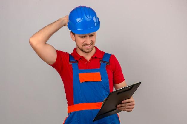 Giovane uomo del costruttore in uniforme della costruzione e lavagna per appunti della tenuta del casco di sicurezza che pensa con lo sguardo confuso della mano sulla testa che ha dubbi sopra la parete bianca isolata