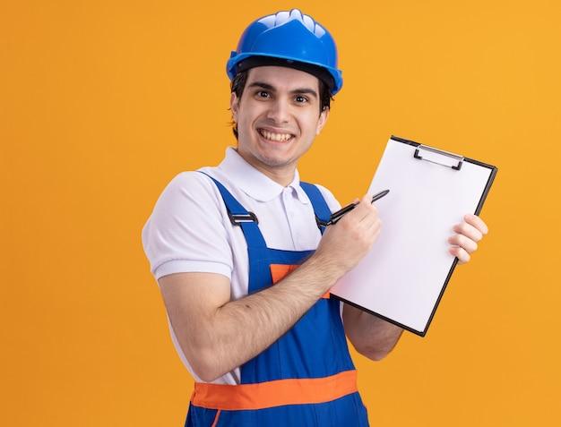 Uomo giovane costruttore in uniforme da costruzione e casco di sicurezza che tiene appunti con la penna guardando la parte anteriore con il sorriso sul viso in piedi sopra la parete arancione