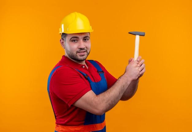Uomo giovane costruttore in uniforme da costruzione e casco di sicurezza che tiene martello cercando fiducioso