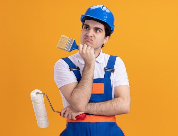 Uomo del giovane costruttore in uniforme da costruzione e casco di sicurezza che tiene il pennello e il rullo che guarda da parte perplesso in piedi sopra la parete arancione