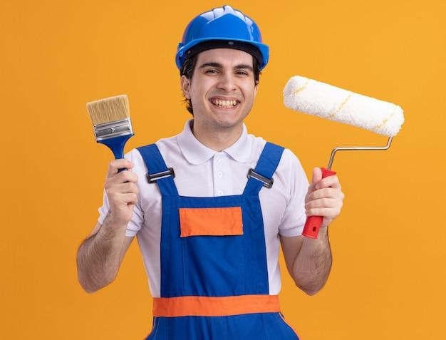 Uomo del giovane costruttore in uniforme da costruzione e casco di sicurezza che tiene il pennello e il rullo guardando la parte anteriore sorridendo allegramente in piedi sopra la parete arancione