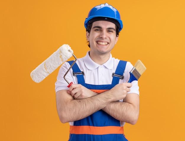 Uomo giovane costruttore in uniforme da costruzione e casco di sicurezza che tiene il pennello e il rullo guardando la parte anteriore con un grande sorriso sul viso in piedi sopra la parete arancione
