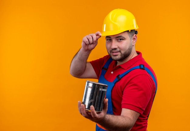 Young builder man in construction uniform and safety helmet holding paint can looking confident with smile touching helmet