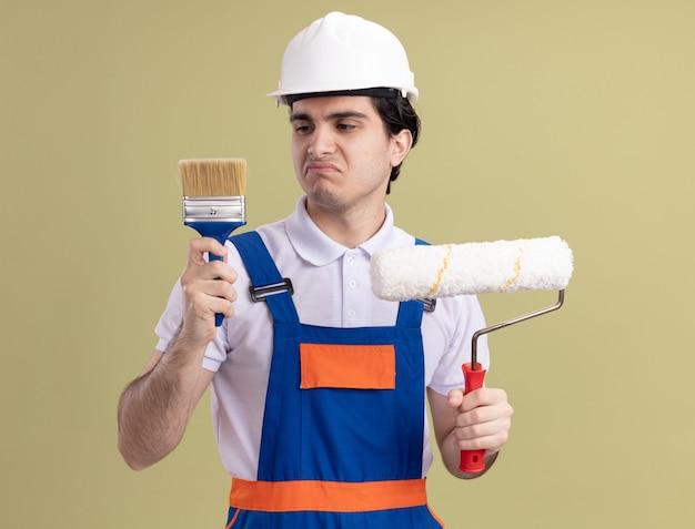 Uomo del giovane costruttore in uniforme da costruzione e casco di sicurezza che tiene il rullo di vernice e il pennello che sembra confuso avendo dubbi in piedi sopra la parete verde