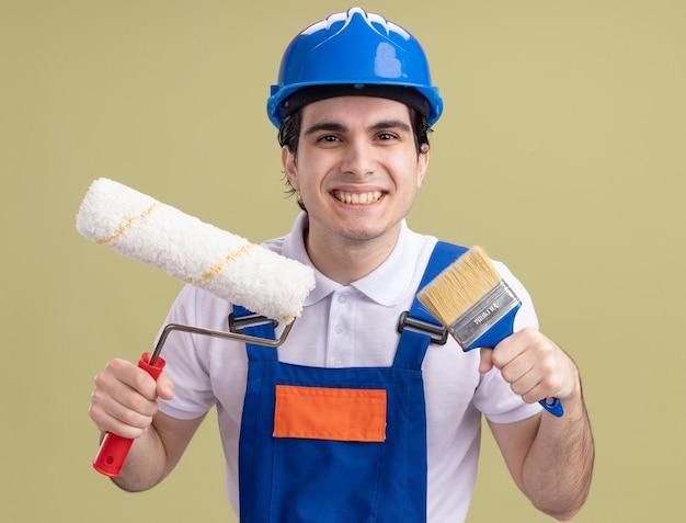 Giovane uomo del costruttore in uniforme da costruzione e casco di sicurezza che tiene il rullo di vernice e pennello guardando la parte anteriore sorridente largamente in piedi sopra la parete verde