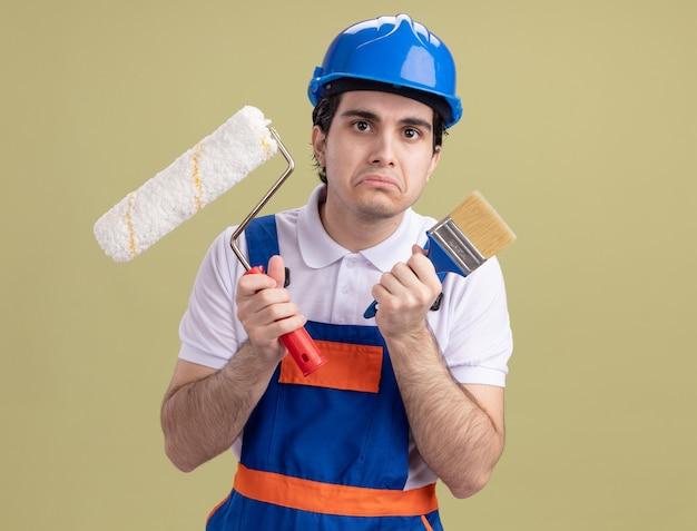 Uomo giovane costruttore in uniforme da costruzione e casco di sicurezza che tiene il rullo di vernice e pennello guardando davanti con espressione triste che increspa le labbra in piedi sopra la parete verde