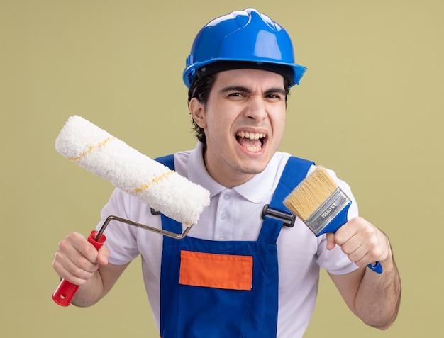 Giovane costruttore in uniforme da costruzione e casco di sicurezza che tiene il rullo di vernice e pennello che grida con espressione aggressiva in piedi sopra la parete verde