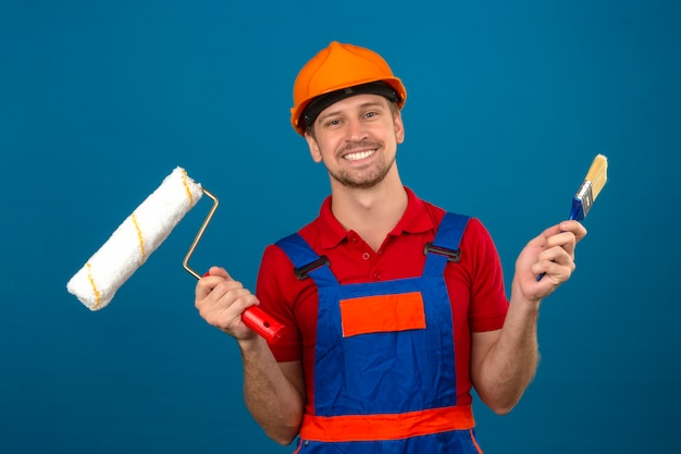 Young builder man in construction uniform and safety helmet holding paint roller and brush with big smile on face over isolated blue wall