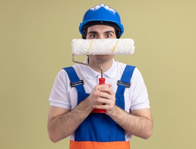 Giovane costruttore in uniforme da costruzione e casco di sicurezza che tiene il rullo di vernice davanti alla sua faccia preoccupata in piedi sopra la parete verde