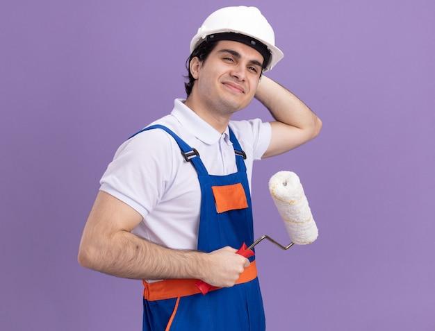 Giovane costruttore in uniforme da costruzione e casco di sicurezza che tiene il rullo di vernice che guarda da parte con la faccia felice in piedi sopra la parete viola
