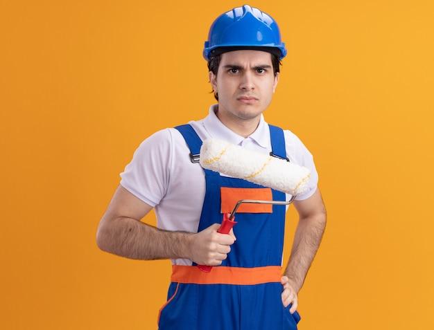 Uomo giovane costruttore in uniforme da costruzione e casco di sicurezza che tiene il rullo di vernice guardando la parte anteriore con la faccia seria in piedi sopra la parete arancione
