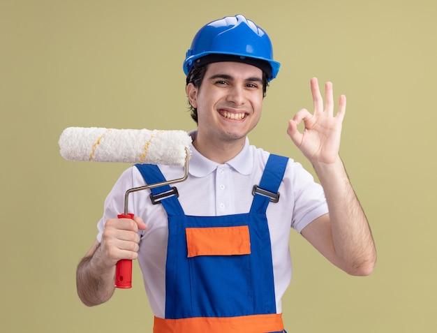 Giovane costruttore in uniforme da costruzione e casco di sicurezza che tiene il rullo di vernice che guarda davanti con il sorriso sul viso che mostra il segno giusto che sta sopra la parete verde