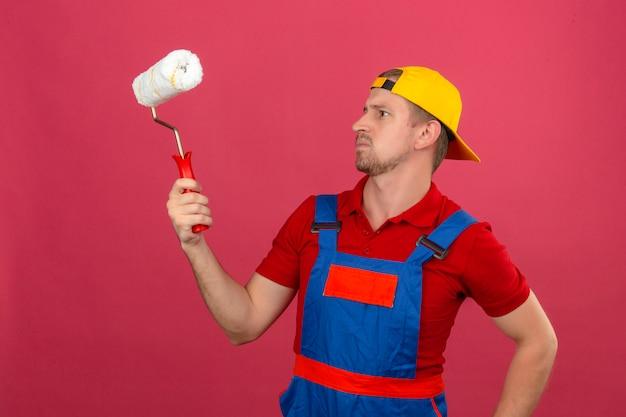 Giovane uomo del costruttore in uniforme della costruzione e rullo di pittura della tenuta del casco di sicurezza e guardarlo con l'espressione scettica sopra la parete rosa isolata
