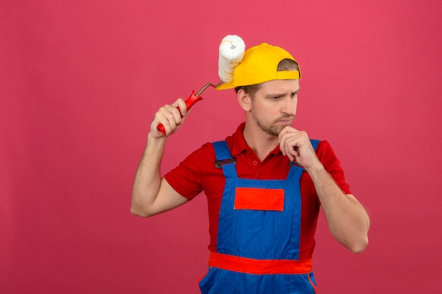 Giovane uomo del costruttore in uniforme della costruzione e rullo di pittura della tenuta del casco di sicurezza che pensa sopra la nuova idea sopra la parete rosa isolata