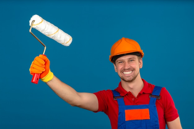 Young builder man in construction uniform and safety helmet holding paint roller and with big smile on face over isolated blue wall