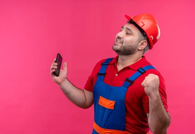 Giovane costruttore in uniforme da costruzione e casco di sicurezza che tiene smartphone pugno di serraggio felice ed è uscito rallegrandosi del suo successo