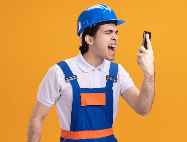 Uomo giovane costruttore in uniforme da costruzione e casco di sicurezza che tiene smartphone gridando con espressione aggressiva in piedi sopra la parete arancione