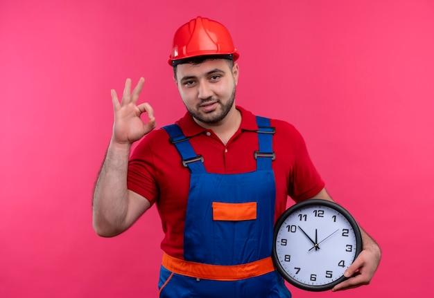 Uomo giovane costruttore in uniforme da costruzione e casco di sicurezza che tiene l'orologio di parete che fa sorridere del segno giusto