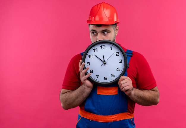 Young builder man in construction uniform and safety helmet holding wall clock hiding behind it peeking over
