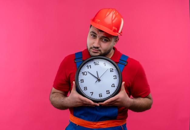 Uomo giovane costruttore in uniforme da costruzione e casco di sicurezza che tiene orologio da parete che guarda l'obbiettivo con la faccia infelice