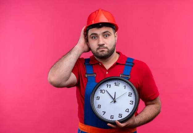 Giovane costruttore in uniforme da costruzione e casco di sicurezza che tiene l'orologio da parete che sembra confuso e sorpreso