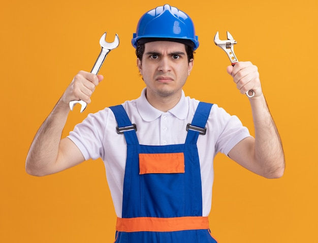 Giovane uomo del costruttore in uniforme da costruzione e casco di sicurezza che tiene le chiavi guardando la parte anteriore con la faccia arrabbiata in piedi sopra la parete arancione