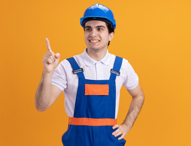 Young builder man in construction uniform and safety helmet looking aside smiling confident pointing with index finger at something standing over orange wall