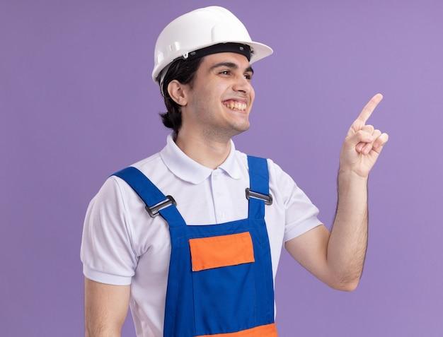 Uomo giovane costruttore in uniforme da costruzione e casco di sicurezza che guarda da parte sorridente che punta con il dito indice a qualcosa in piedi sopra il muro viola