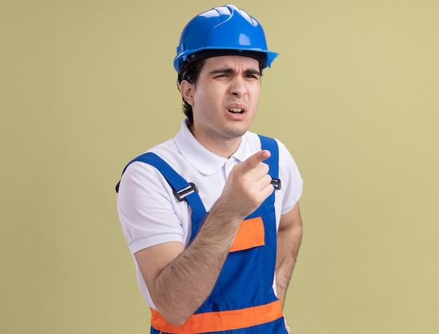 Uomo giovane costruttore in uniforme da costruzione e casco di sicurezza che guarda da parte con espressione confusa che punta con il dito indice a qualcosa in piedi sopra la parete verde